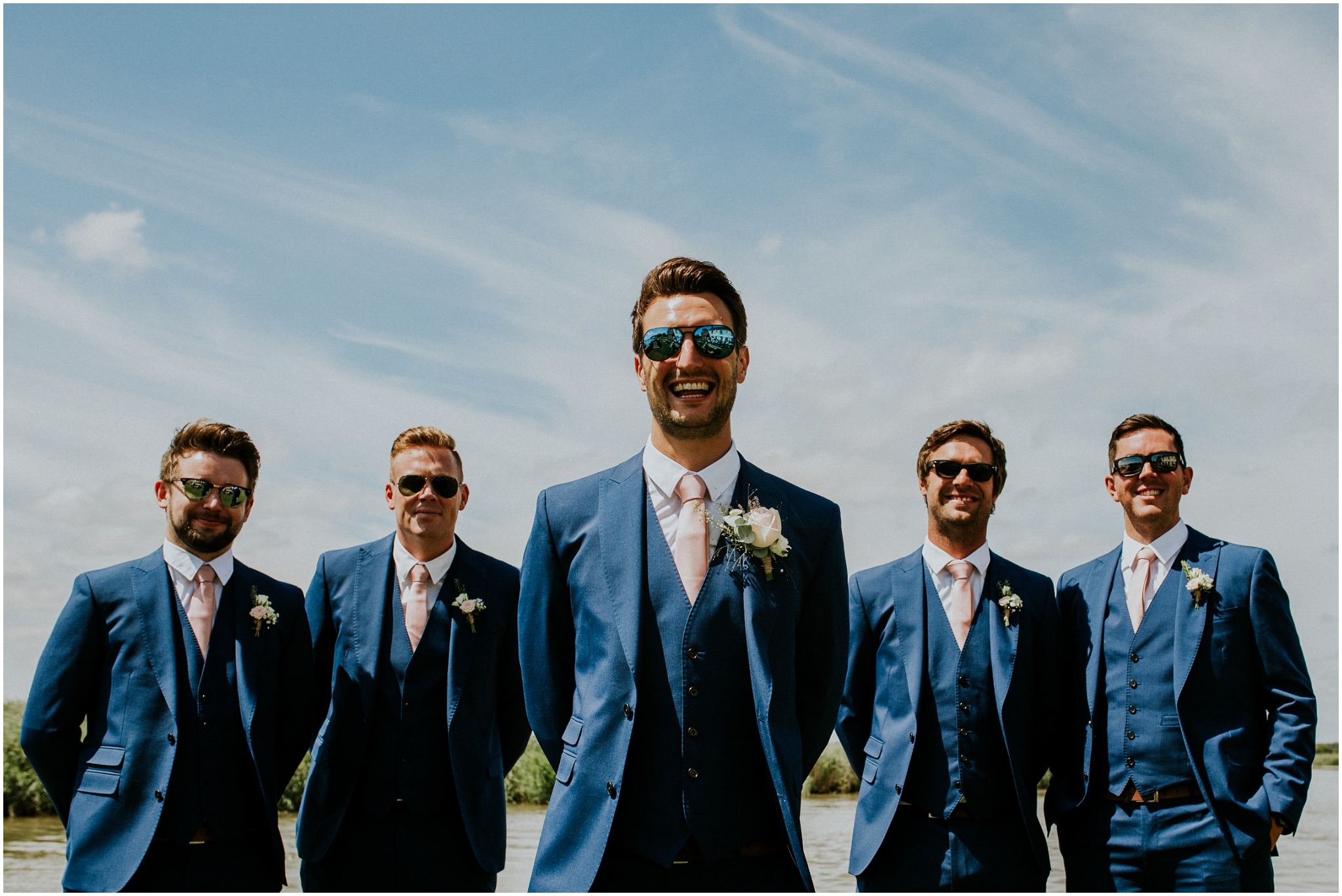 groom and groomsmen wearing sunglasses at the ferry inn stokesby norfolk wedding