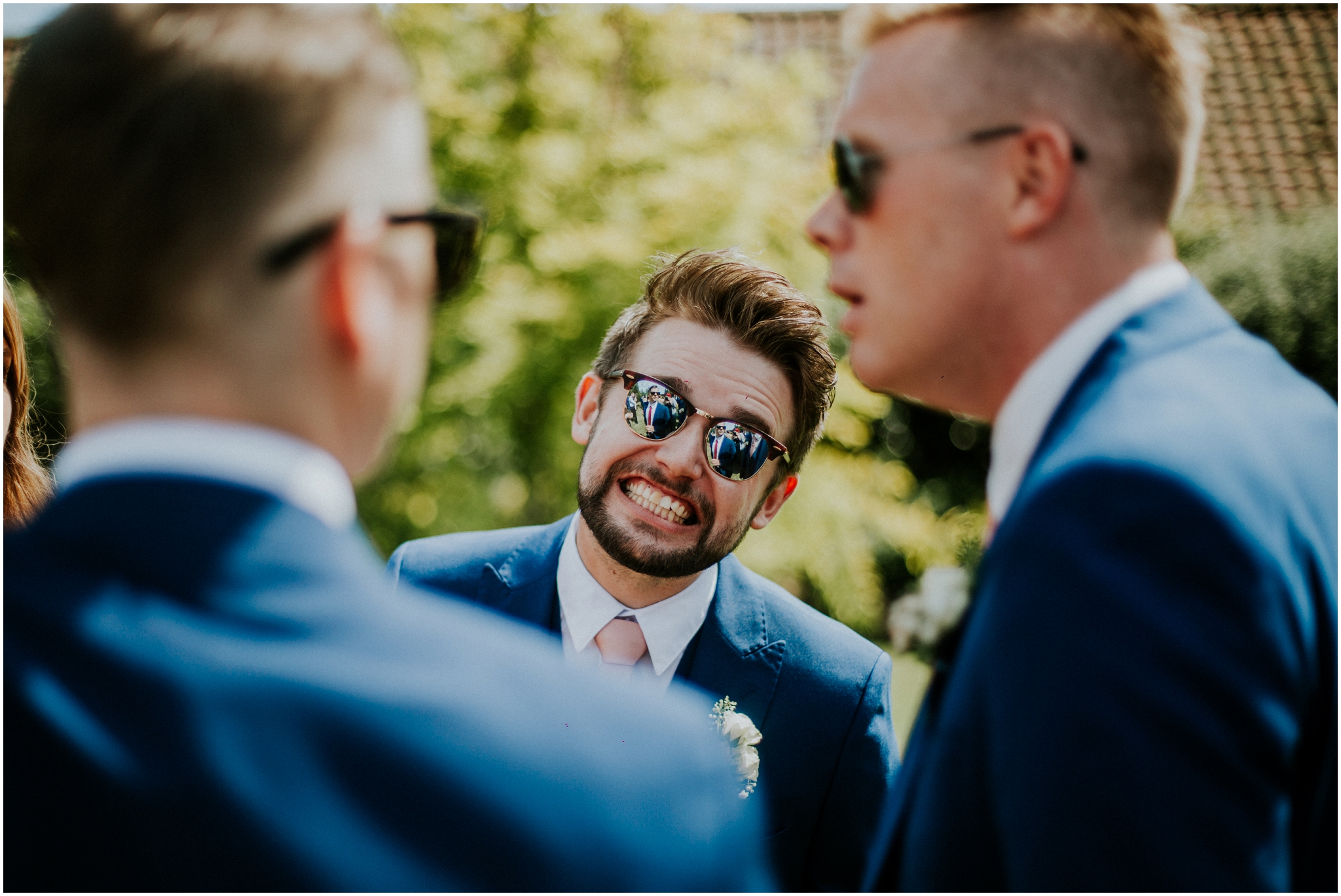 groomsman grinning wearing sunglasses