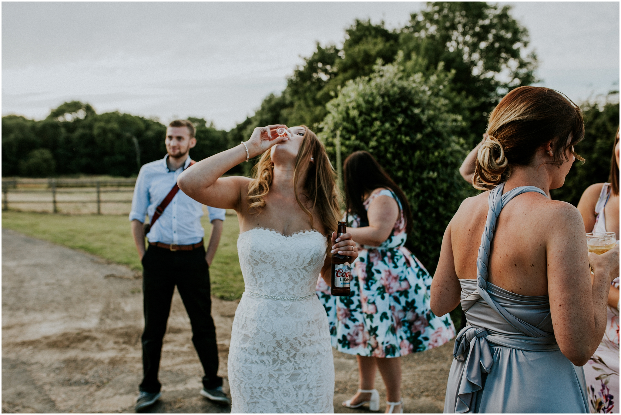 super cool bride doing a shot while holding a beer
