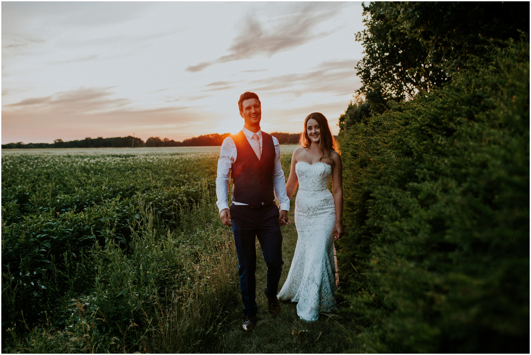 bride and groom holding hands during sunset