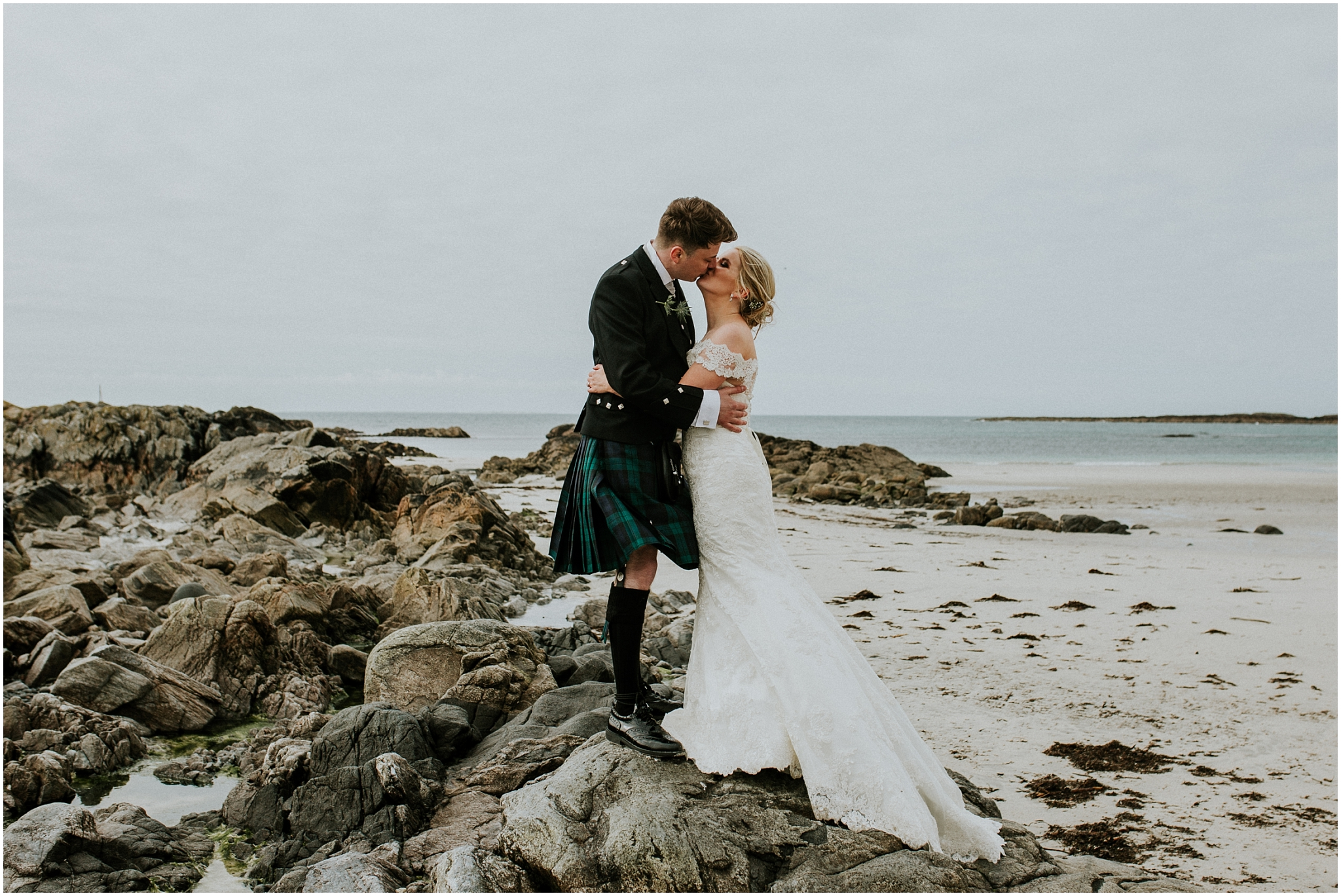 bride and groom kissing on the rocks