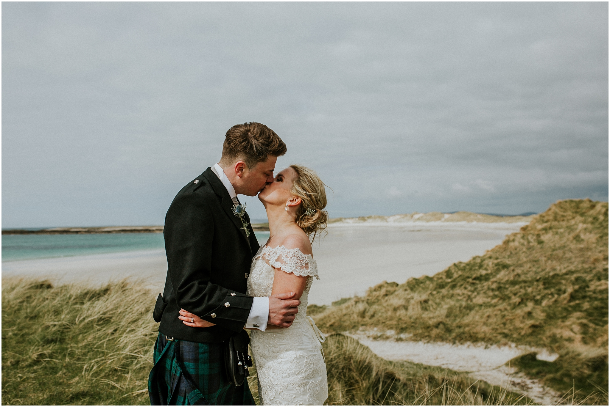 bride and groom kissing on the dunes
