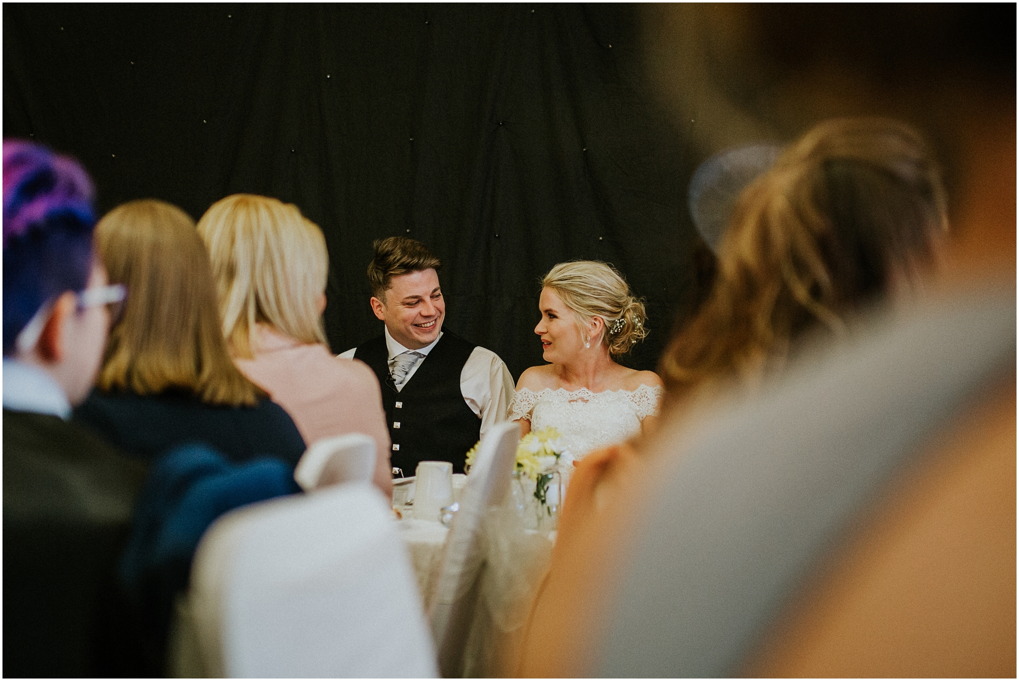 bride and groom looking at each other laughing