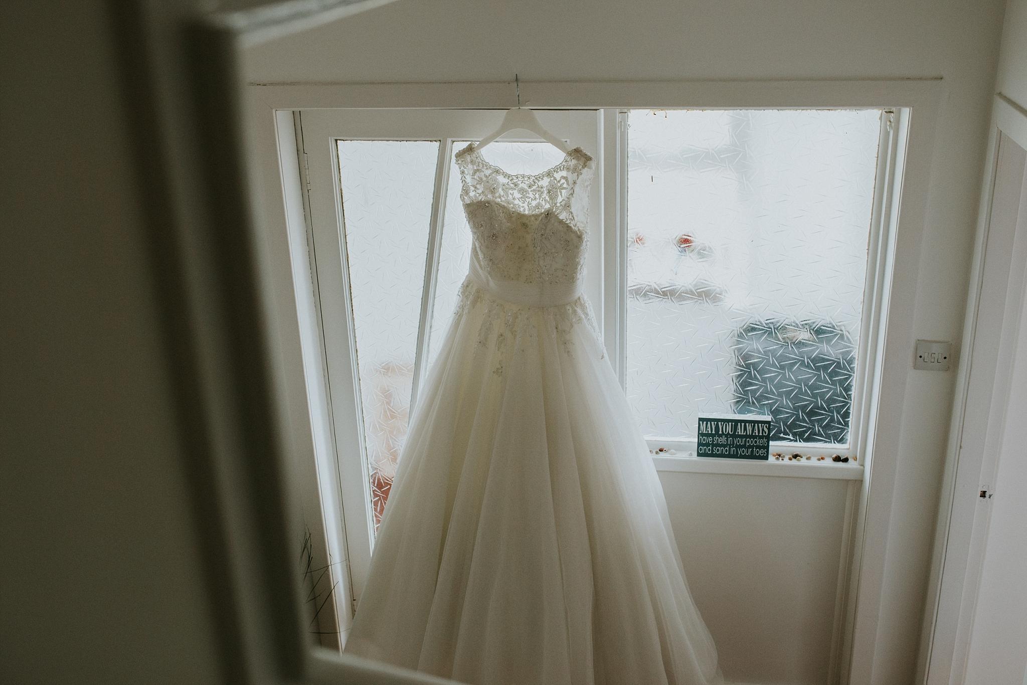 Wedding dress hanging in doorway