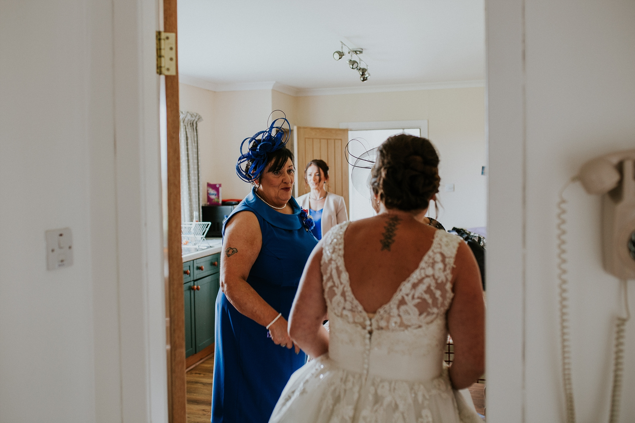 mother of the groom looking at bride in her dress