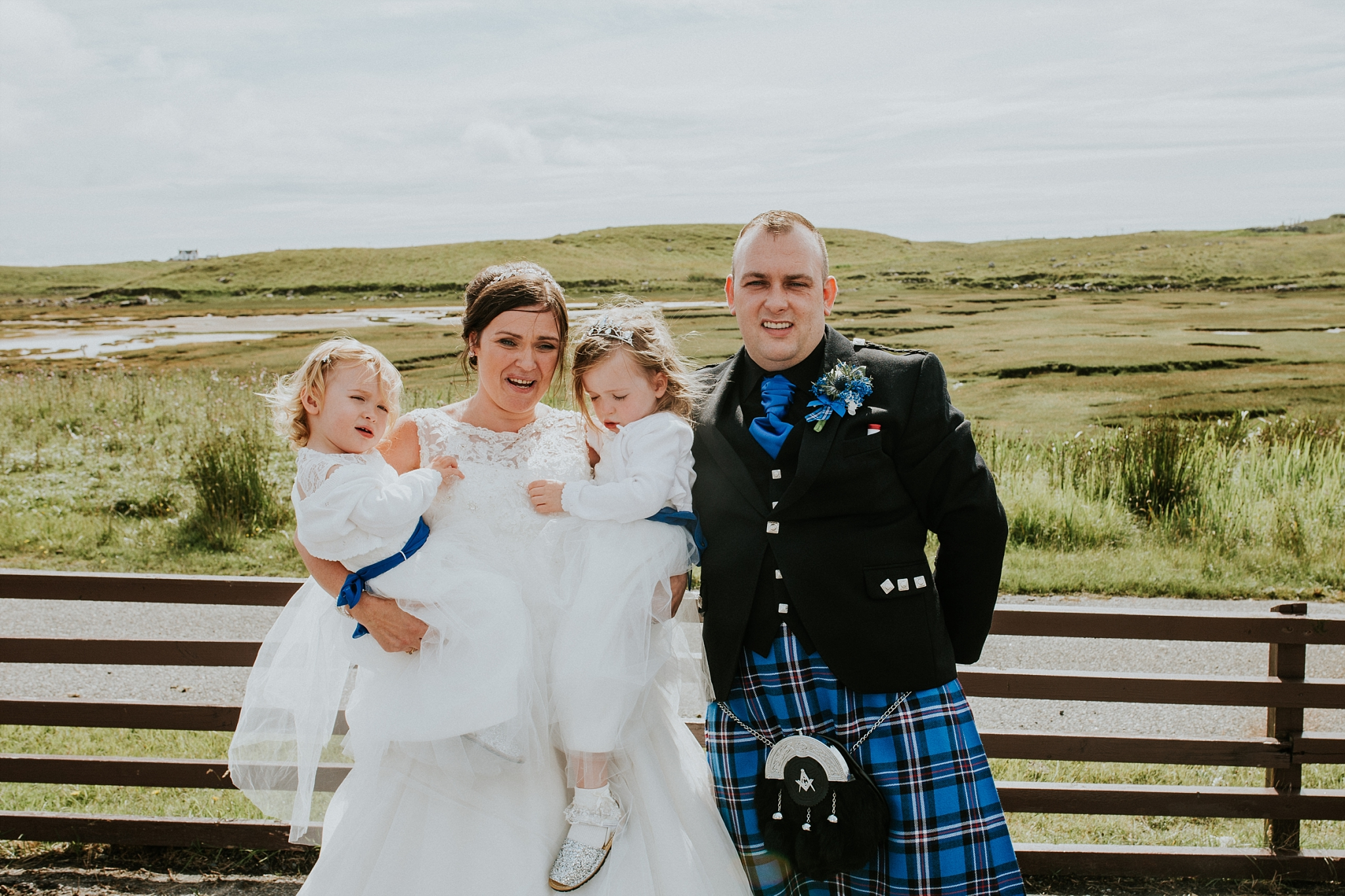 bride and groom with two flower girls, family photo