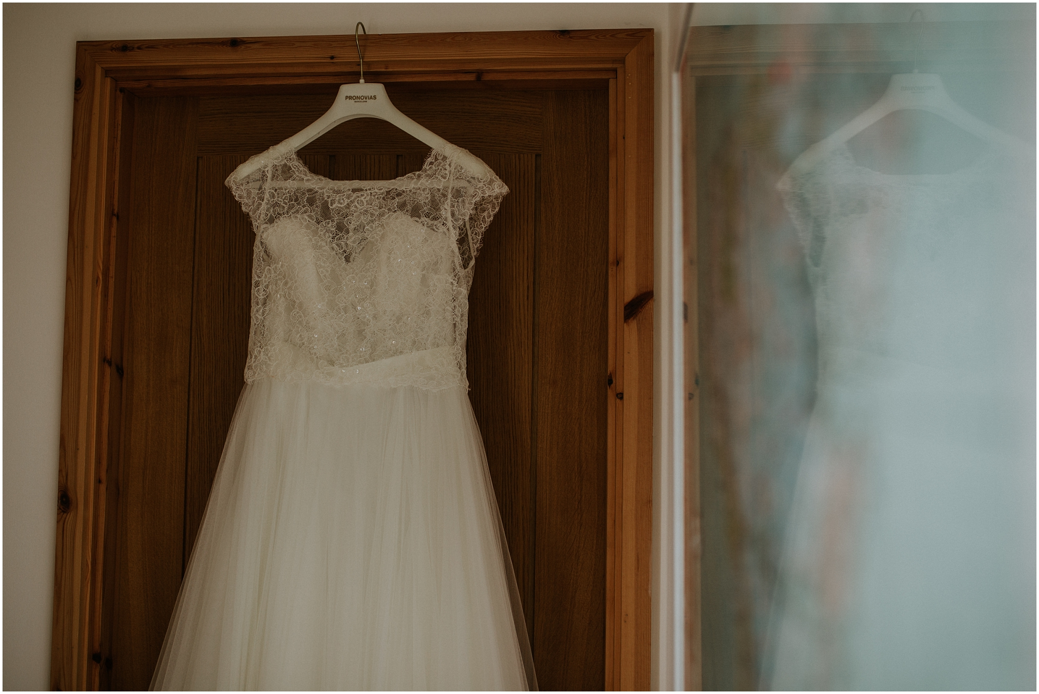 wedding dress hanging up in doorway